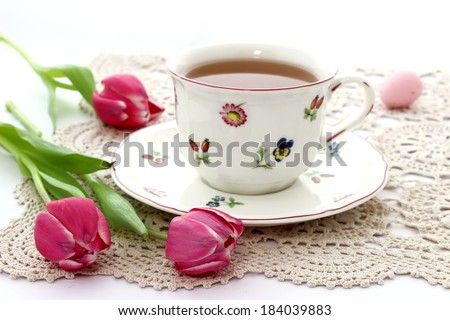 cup of tea and tulips on beautiful napkin - stock photo
