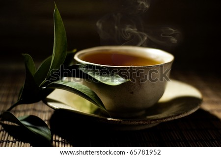 cup of tea and twig with dark background - stock photo