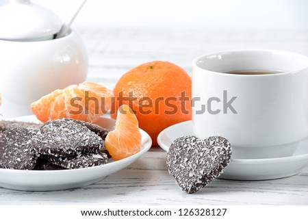 Cup of tea, chocolate chip cookies  in the form of heart and tangerines - stock photo