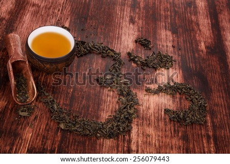 Cup of tea, dry tea leaves forming ohm symbol and buddhist necklace. Traditional tea drinking. - stock photo