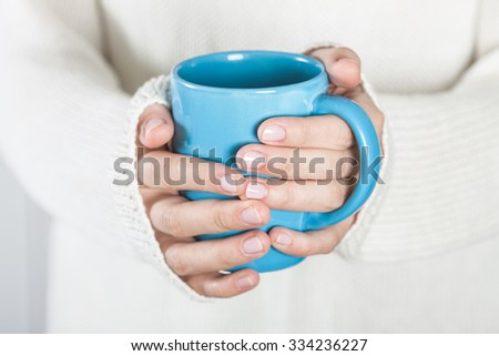 Cup of tea or coffee in female hands close up. Cold weather concept. - stock photo