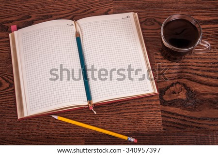 cup of tea, pen, opened organizer on the wooden table.  Blue toned - stock photo