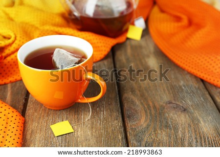 Cup of tea, teapot and tea bags on wooden table close-up - stock photo