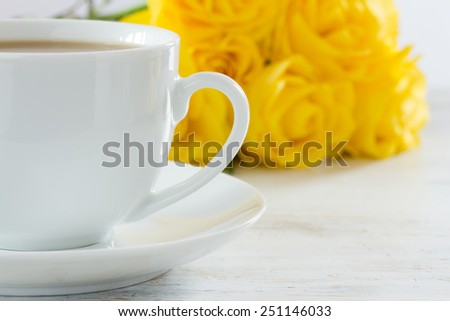 Cup of tea with a bouquet of yellow roses - stock photo