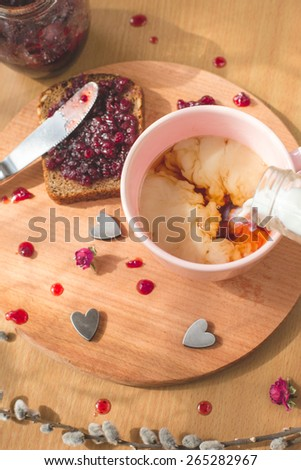 Cup of tea with a pouring milk, fresh baked homemade healthy bread with blackcurrant jam - homemade marmalade with fresh organic fruits from garden. In rustic decoration, fruit jam bread wooden table - stock photo