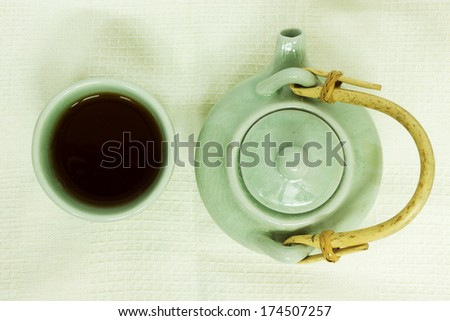 Cup of tea with a teapot on white tablecloth. - stock photo