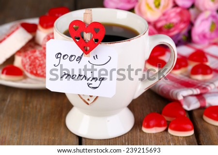 Cup of tea with card that says good morning on table close-up - stock photo