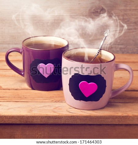 Cup of tea with chalkboard stickers and heart shape on wooden table - stock photo