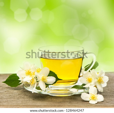 cup of tea with jasmine flowers on wooden table over blurred green background - stock photo