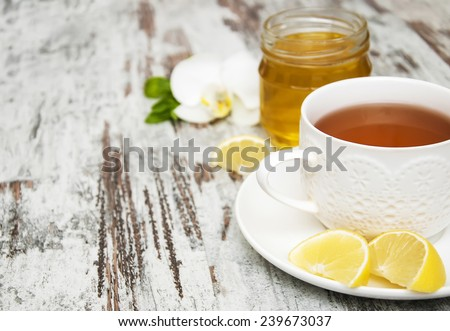 Cup of tea with lemon and honey on wooden background - stock photo
