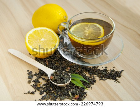 cup of tea with lemon over wooden background - stock photo