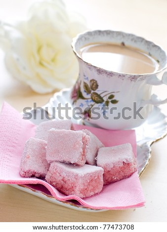 Cup of tea with milk served with strawberry cake. Selective focus - stock photo