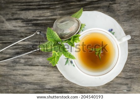 Cup of tea with mint and tea strainer on old wooden table, top view  - stock photo