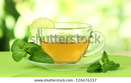 Cup of tea with mint on table on bright background - stock photo