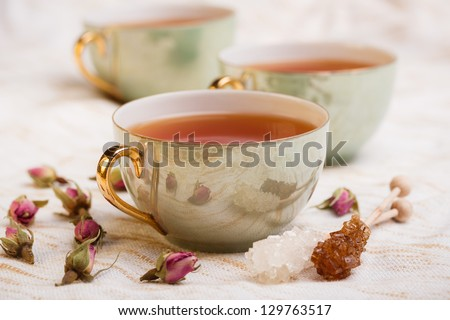 Cup of tea with rose bud and rock sugar sticks - stock photo