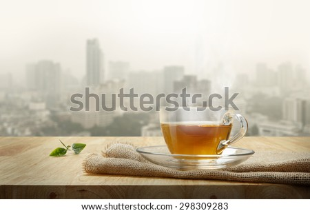 Cup of tea with sacking on the wooden table and the city background - stock photo