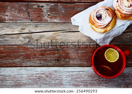 Cup of tea with sweet cake on old wooden background. Top view. - stock photo