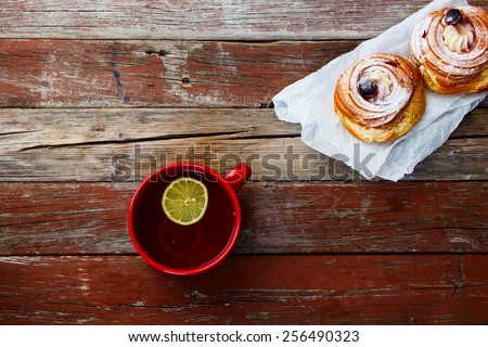 Cup of tea with sweet cake on rustic wooden table. Top view. - stock photo