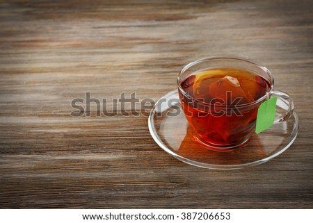 Cup of tea with tea bag on wooden table background - stock photo