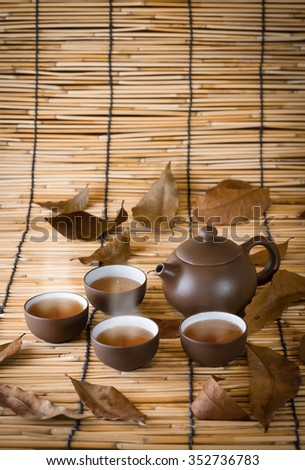 Cup of winter tea cups and dry herbal tea on a bamboo mat background.jpg - stock photo
