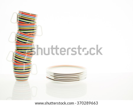 Cup stacking and stack of plates against a white background - stock photo