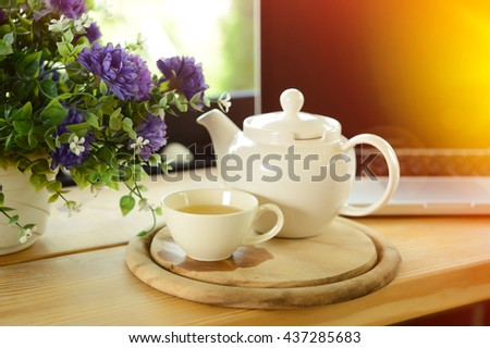 cup, tea pot ,cookies and laptop on wooden desk on cofe, business concept - stock photo