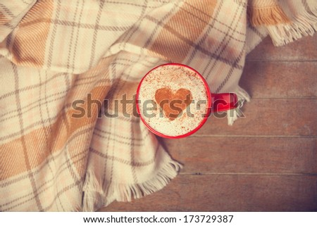 Cup with coffee and shape of the cacao heart on it and scarf. Photo with focus on heart. - stock photo
