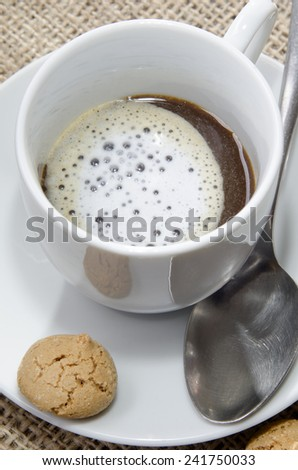 cup with coffee, milk foam and biscuit - stock photo