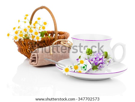 Cup with fresh camomile flower and tea bags, isolated on white - stock photo