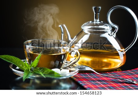 Cup with green tea and green leaves.  - stock photo