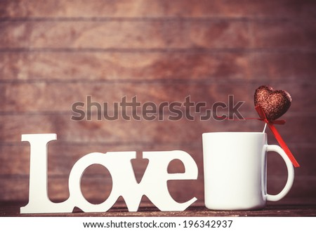 Cup with heart shape and word Love on table. - stock photo