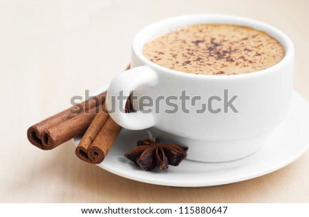 Cup with hot cappuccino decorated with spices including cinnamon sticks and star anise. - stock photo