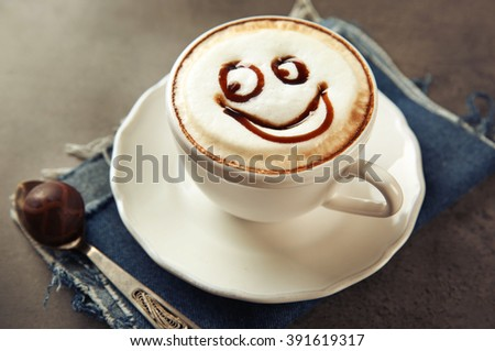 Cup with hot cappuccino with chocolate syrup and candy on grey table - stock photo