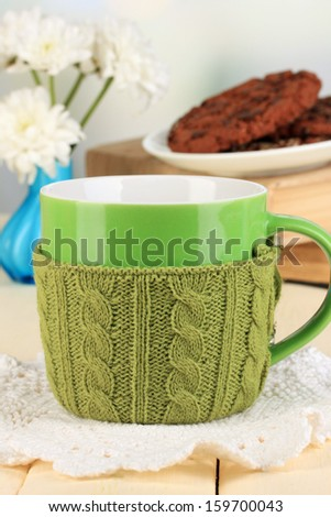 Cup with knitted thing on it close up - stock photo