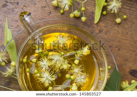 cup with linden tea and flowers on wooden table  - stock photo