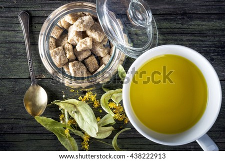 cup with linden tea on wooden table - stock photo
