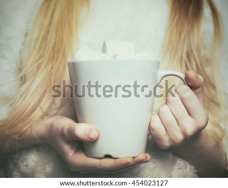 cup with marshmallows  in female hands - stock photo