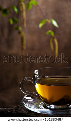 Cup with tea and birch branch with seeds , young leaflets - stock photo