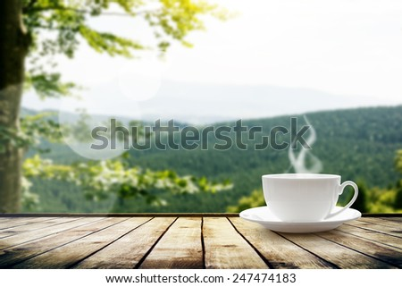 Cup with tea on table over mountains landscape with sunlight. Beauty nature background - stock photo