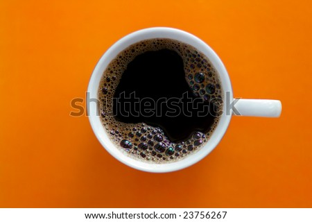 Cup with the coffee against the orange background - stock photo