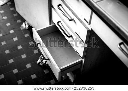 Cupboard with opened empty drawer closeup photo - stock photo