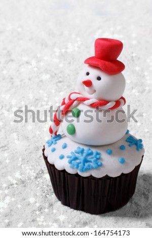 Cupcake Christmas snowman on white snow. vertical - stock photo