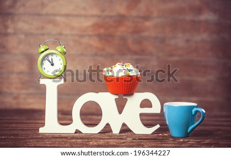 Cupcake, coffee, alarm clock and word Love on wooden table. - stock photo