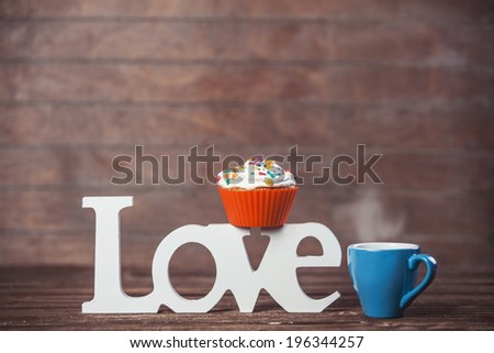 Cupcake, coffee and word Love on wooden table. - stock photo