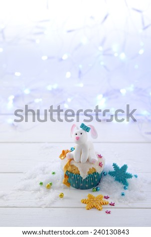 Cupcake decorated a sugar rabbit with blue bow on a bright lights background vertical format. - stock photo