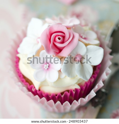 Cupcake decorated with fondant flowers - stock photo