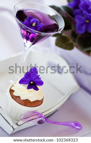 Cupcake decorated with whipped cream and violet flowers and cocktail, selective focus - stock photo