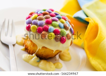 cupcake doused with white chocolate and decorated with smarties - stock photo
