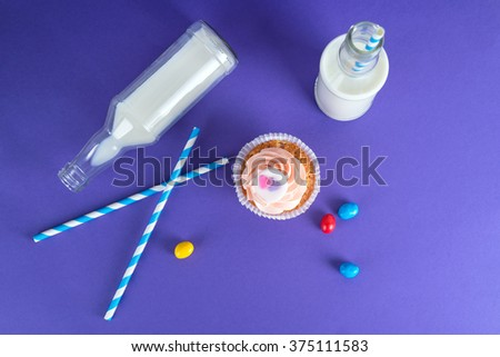 Cupcake for Valentine's Day with hearts on top of whipped cream and milk cocktails with retro cocktail tubes, served in bottles on colorful background - stock photo