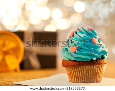 Cupcake - shallow DOF. Christmas lights and gifts in the background. - stock photo